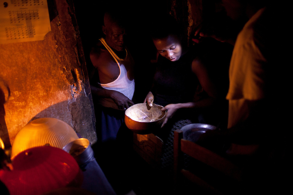 The Clotaire family prepares dinner in their home on July 15, 2010 in Gador, Haiti.
