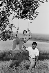 Two men on a swing in the country