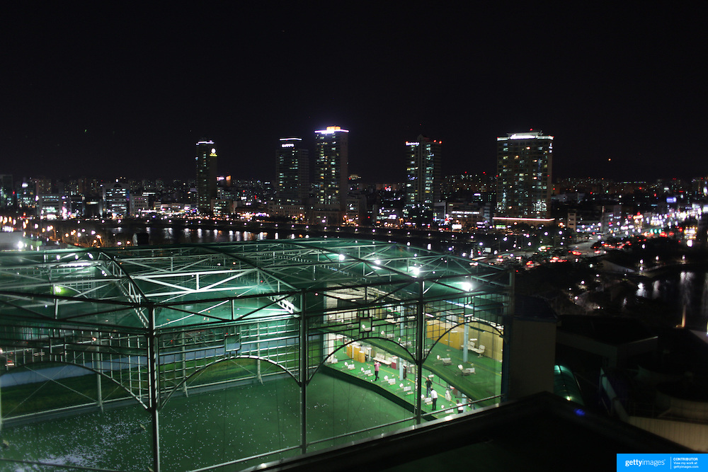The Lotte World Hotel indoor golf driving range viewed at night with the city in the background. Seoul, South Korea. 21st March 2012. Photo Tim Clayton