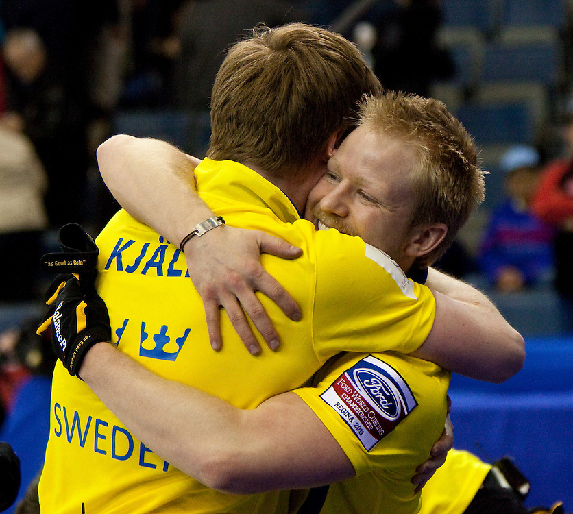 Swedish skip Niklas Edin, right, hugs lead Viktor Kjaall as they celebrate their  7-6 win over Norway in the bronze medal match at the Ford World Men's Curling Championships in Regina, Saskatchewan, April 10, 2011.<br /> AFP PHOTO/Geoff Robins