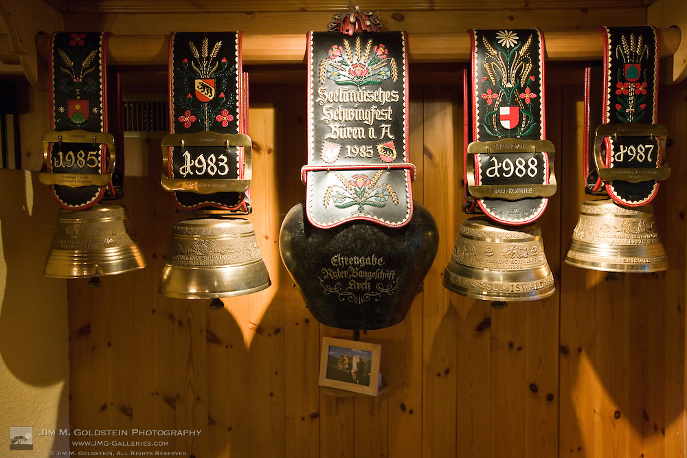 Cowbell awards hang in the lobby of a hotel with the photo of the winning cow