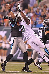 Aug 26, 2012; East Rutherford, NJ, USA; Carolina Panthers quarterback Cam Newton (1) is hit by New York Jets defensive end Quinton Coples (98) while throwing a pass during the first half at MetLife Stadium.