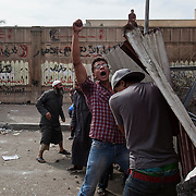 A mix of Islamists and revolutionary youth activists lob stones and chunks of concrete from cover behind makeshift shields as they battle Egyptian security forces during May 4, 2012 demonstrations against the ruling Supreme Council of the Armed Forces (SCAF) near the Defense ministry building in the Abbasiya district of Cairo. Close to 300 people were injured in the clashes, one killed, and an estimated 300 people arrested by the military.
