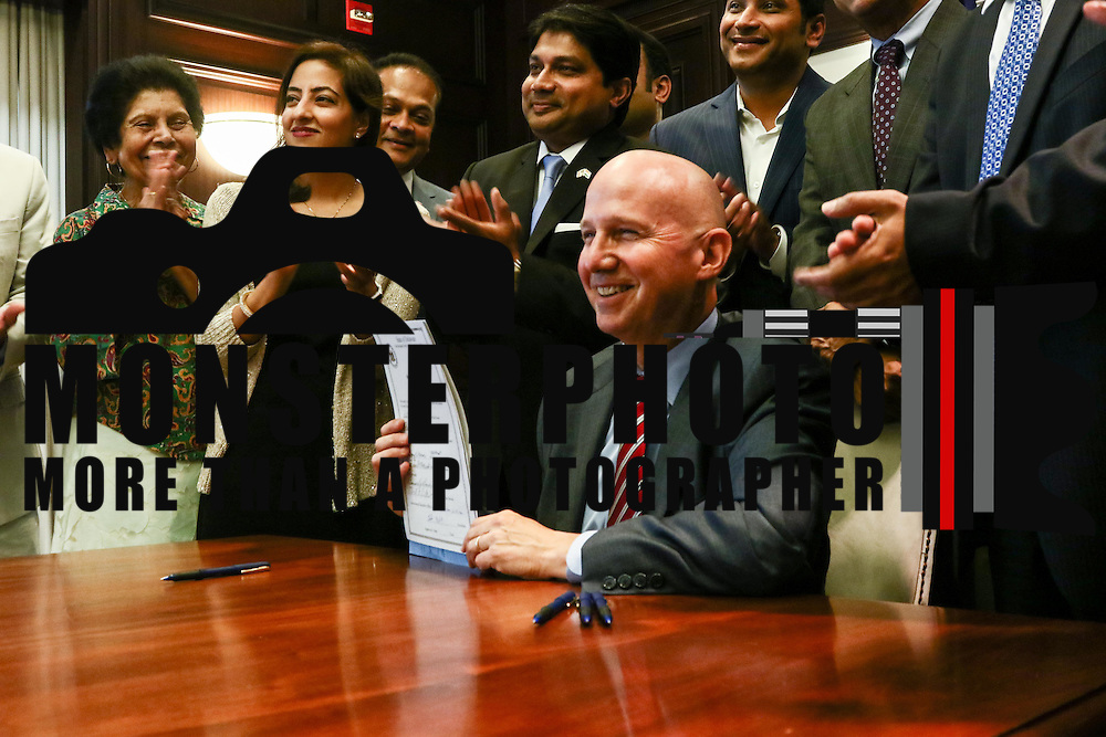 Gov. Markell (CENTER) poses for photos after signing into law the creation of a Commission on Indian Heritage and Culture whiles members of Delaware's Indian committee applause in the background Thursday, Sept. 01, 2016, at the Carvel State Office Building in Wilmington.