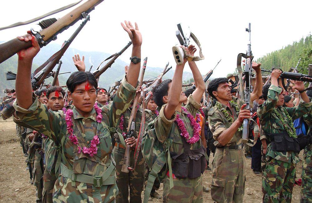 """RUKUM DISTRICT, NEPAL, APRIL 22, 2004:  A battalion of Maoist insurgents gather in Rukum district April 22, 2004 weeks after their attack on government troops in Beni when they overran the district headquarters, looting a bank, destroying the jail and torching government office buildings. The government said that 32 security personnel died in the clash and 37 were kidnapped. The clash was one of the deadliest since 1996 when fighting began to topple the constitutional monarchy and install a communist republic. The guerrillas' strength is hard to gauge. Analysts and diplomats estimate there about 15,000-20,000 hard-core fighters, including many women, backed by 50,000 """"militia"""".  In their remote strongholds, they collect taxes and have set up civil administrations, and """"people's courts"""" to settle rows. They also raise money by taxing villagers and foreign trekkers. Though young, they are fearsome fighters and  specialise in night attacks and hit-and-run raids. They are tough in Nepal's rugged terrain, full of thick forests and deep ravines and the 150,000 government soldiers are not enough to combat this growing movement that models itself after the Shining Path of Peru. (Ami Vitale/Getty Images)"""