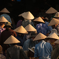 Women gather at the fish market along the Hoi An River at daybreak.