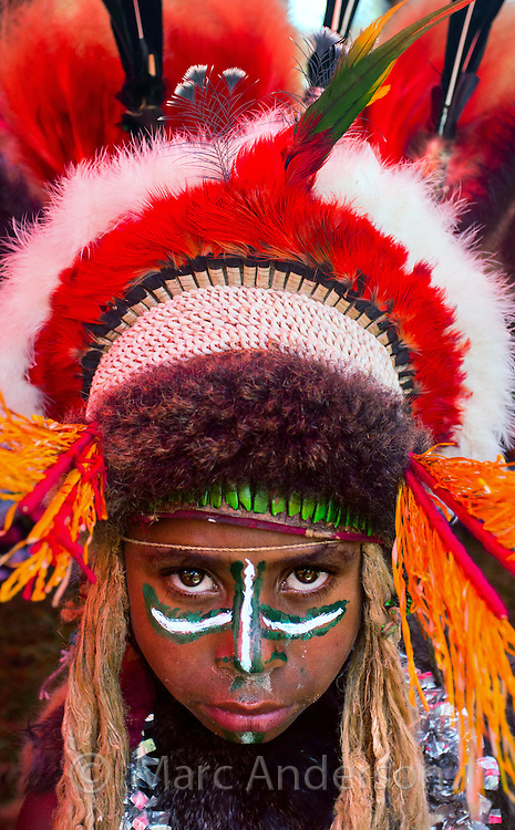 Young girl with her face painted and wearing a large traditional headdress at the Goroka show in Papua New Guinea.