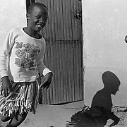 A young girl laughs with joy and relief as she runs out of the room where she was examined for virginity by a group of mothers in Magqabasini village, near Flagstaff in the former Transkei July 20, 1999.  This tradition has been revived to combat child abuse and high rates of teenage pregnancies and the spread of HIV. (Greg Marinovich)