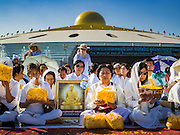 "02 JANUARY 2016 - KHLONG LUANG, PATHUM THANI, THAILAND:   People with a picture of the Abbot of Wat Phra Dhammakaya pray while they wait for the start of a mass pilgrimage of Buddhist monks at Wat Phra Dhammakaya on the first day of the 5th annual Dhammachai Dhutanaga (a dhutanga is a ""wandering"" and translated as pilgrimage). More than 1,300 monks are participating pilgrimage through central Thailand. The purpose of the pilgrimage is to pay homage to the Buddha, preserve Buddhist culture, welcome the new year, and ""develop virtuous Buddhist youth leaders."" Wat Phra Dhammakaya is the largest Buddhist temple in Thailand and the center of the Dhammakaya movement, a Buddhist sect founded in the 1970s. The monks are using busses on some parts of the pilgrimage this year after complaints about traffic jams caused by the monks walking along main highways.        PHOTO BY JACK KURTZ"