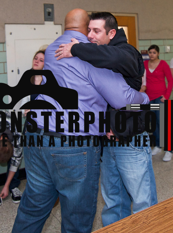 12/22/10 Wilmington DE: Kirk Middle School Principal Mr. Cordie Greenlea (Left) embraces John Sullivan (Right) after john received gifts for his family from students at his late son's school Kirk Middle School in Newark Delaware...Special to Monsterphoto/SAQUAN STIMPSON