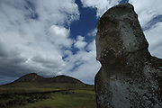 A close-up of a moai standing near Tongariki, in front of the Rano Raraku volcano, along Easter Island's southern coast; clouds gather over the volcano