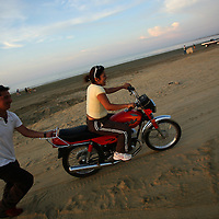 A woman gets motorcycle-riding lesson on a beach in Manta, Ecuador on April 14, 2008. Currently the United States uses an air base in Manta to conduct drug-trafficking surveillance flights. The United States military presence helps to contribute an estimated $6.5 million annually to the local economy, but the Ecuadorian government is looking into the possibility of closing the US base once the lease runs out in 2009. (Photo/Scott Dalton).