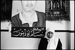 A mother in the Balata refugee camp stands beneath a painting of her son, Hossam Abu Zaitoun, killed by Israeli forces during a protest in the occupied West Bank.