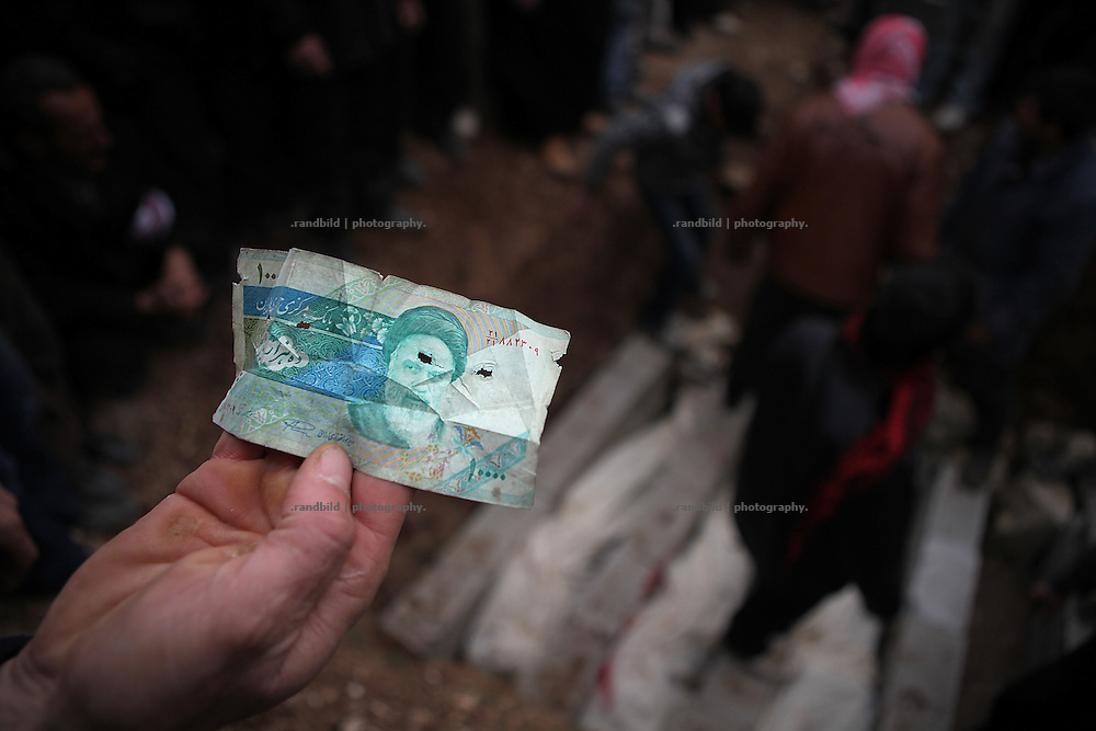 A man shows an iranian bill found after the raid in Kureen. The people take this as an evidence fot the involment of iranian counter-revolutionarie in Syria. About two thousand inhabitants of Kureen, Province of Idlib, Syria, gather for the funeral of four men and one woman killed yesterday during a full scale military attack on the village.