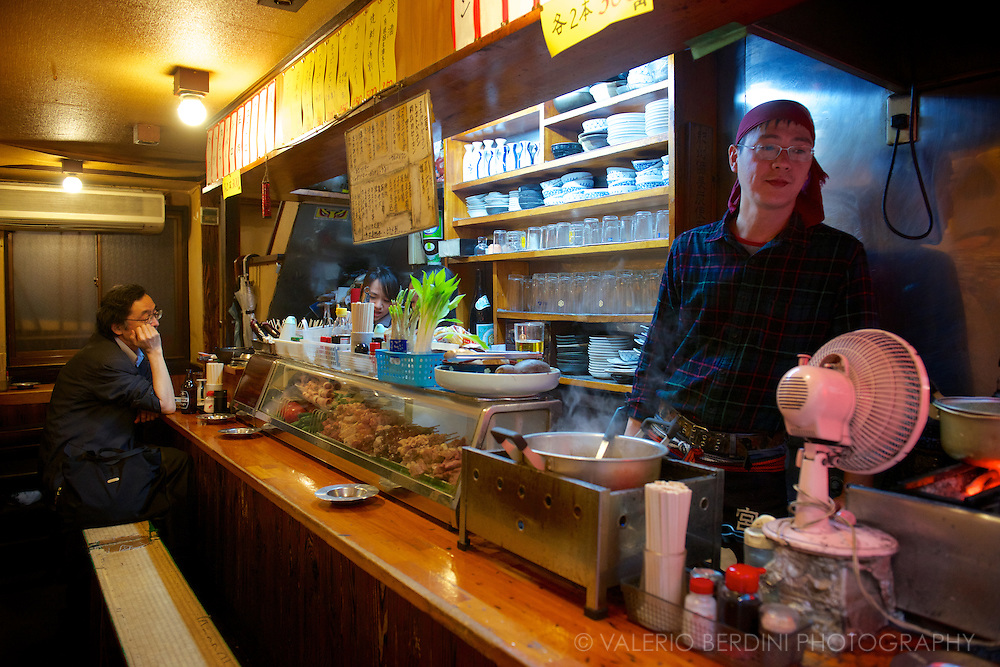 A chef waits for his clients to sit on the only bench available in another of the restaurants of Memory Lane. Food is freshly prepared, often grilled with traditional japanese ingredient and sauces. Shinjuku, Toyko, Japan.