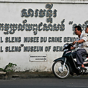 A couple on a motorcycle ride past the Toul Sleng Genocide Museum in Phnom Penh, Cambodia, March 13, 2005.  According to government sources about 500 people a day visit the museum where an estimated 14,000 people were tortured and later executed.  The building was a high school in Phnom Penh before being used as a prison by the Khmer Rouge in 1975.