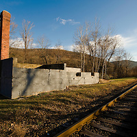 Foundation and chimney along railroad tracks.