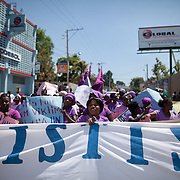 "Women carry a banner demanding ""Social Justice,"" as they sing and dance through downtown Port-au-Prince. (Photo by Ben Depp)"