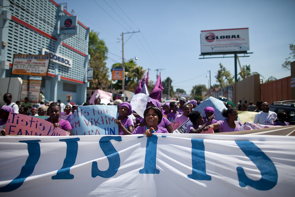 """Women carry a banner demanding """"Social Justice,"""" as they sing and dance through downtown Port-au-Prince. (Photo by Ben Depp)"""