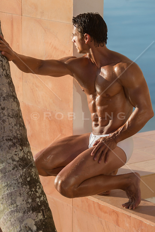 muscular man in a speedo outdoors in a window frame