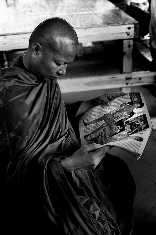 A Monk with a taste for Thai Boxing drops by the Muay Thai Boxing Club under the freeway at Khlong Toei, Bangkok Thailand March 2003.©David Dare Parker/AsiaWorks Photography