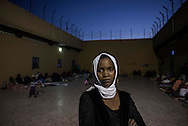 Libya, Garabulli: Ahua, from Niger is seen as she stands in the courtyard of Alguaiha detention center where migrants captured at the sea as they were attempting to reach Italy are kept, on May 12, 2015. Alessio Romenzi