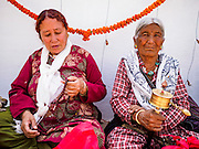 07 MARCH 2017 - KATHMANDU, NEPAL: Nepalese Buddhist women pray during the consecration ceremony at Boudhanath Stupa. Boudhanath Stupa, the most important Buddhist site in Nepal and a popular tourist attraction, was consecrated Tuesday in a ceremony attended by thousands of Buddhist monks and Buddhist people from Nepal and Tibet. The stupa was badly damaged in the 2015 earthquake that devastated Nepal. The stupa, which reopened in November 2016, was repaired in about 18 months. The repair was financed by private donations raised by international Buddhist organizations.     PHOTO BY JACK KURTZ
