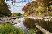 Fall colors reflect in Mill Creek, upstream of Lower Falls in Cataract Falls State Recreation Area, an hour southwest of Indianapolis, near Cloverdale, Indiana, USA. Autumn foliage colors were brilliant but water volume was low for this photo in mid October 2015. The park's limestone outcroppings formed millions of years ago when the region was covered by a large shallow ocean.