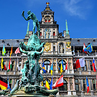 Stadhuis and Brabo Fountain in Antwerp, Belgium <br /> The centerpiece of Grote Markt square is Stadhuis, a mid-16th century, Renaissance city hall that&rsquo;s decorated with colorful flags.  Below the Virgin Mary statue is the Hapsburg coat of arms, a Spanish dynasty that ruled central Europe in the 16th and 17th centuries.  More interesting is the 1887 statue of hero Silvius Brabo who liberated sailors from paying tolls after defeating a giant named Druon Antigoon.  He&rsquo;s about to throw his enemy&rsquo;s severed hand into the Schelde river.  The Flemish word for this is handwerpen which, according to legend, is how Antwerp got its name.