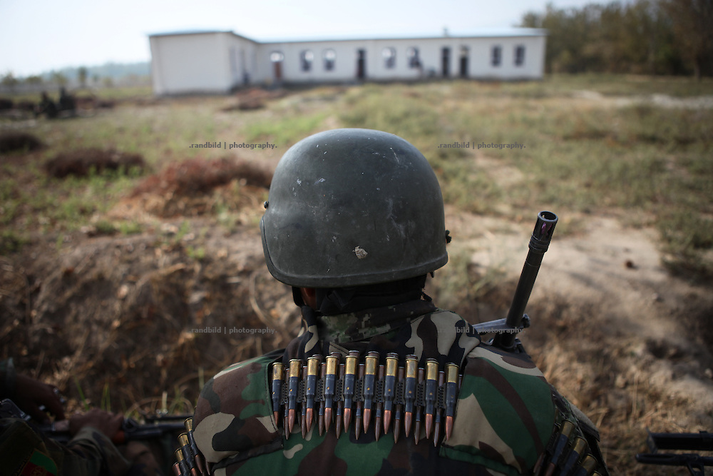 A afghan soldier with ammunition on his back. In background the joint boys and girls school in Mama Khel. Joint patrol of german Bundeswehr and Afghan National Army in and around Nawabad. By rising presence ISAF wants to push out remain Taliban and occupy the former insurgent held region of Chahar Darah. Soldiers talk to local, recruit informers, check cars and try to figure out essential needs of Nawabads local polupaltion. late October 2011 Kunduz based 3.Task Force started a several days operation in and around Nawabad (District Chahar Darah), west of Kunduz, northern Afghanistan. During the Operation Orpheus about 100 german infantery soldiers rolled out for patrols through the town and surrounding areas, which were expected as a retreat zone of insurgents.