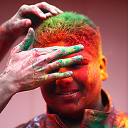 A participant is covered in gulal, or powdred color, during a Holi festival at the Sanatan Dharma Hindu Temple and Cultural Center in Maple Valley on Saturday, March 10, 2012. Holi, the Festival of Colors, is a Hindu festival welcoming spring. It is most well-known for the vibrant bursts of gulal, the powdered dye, that festivalgoers throw on each other. (Joshua Trujillo, seattlepi.com)