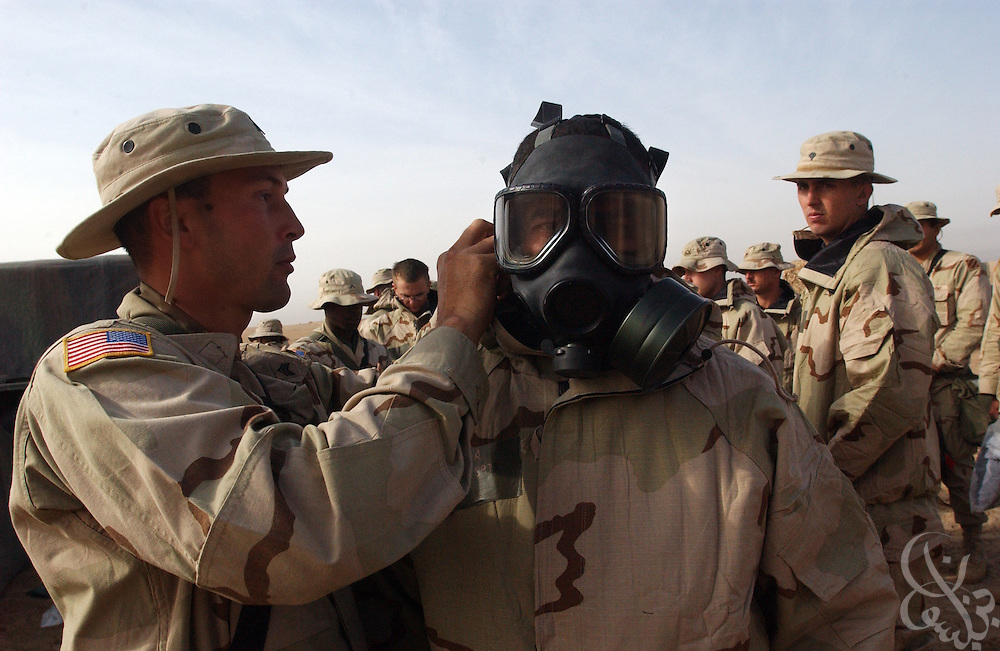 U.S. Army 3rd Infantry Division Task Force Sergeant Brian Torres (L), from Ft. Lauderdale, Florida, helps Specialist Jose Larra, from Cayuas, Puerto Rico, fit his gas mask during a chemical warfare training exercise March 12, 2003 near the Iraqi border in northern Kuwait.