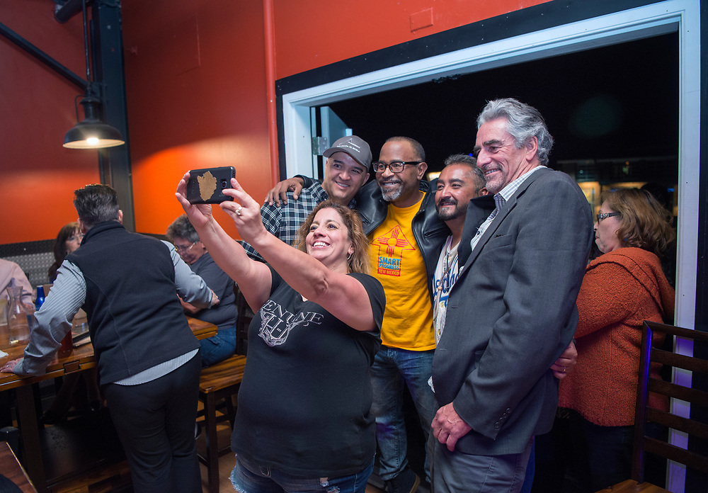 em050217l/a/President of the Santa Fe Chamber of Commerce Simon Brackley, right, City Councilor Ron Trujillo, second from right, and others take a photo as the results of the soda tax election come in. They were at a party by Smart Progress New Mexico at the Boxcar in Santa Fe, Tuesday May 2, 2017. Trujillo opposed the tax. (Eddie Moore/Albuquerque Journal