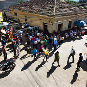 A view of La Esperanza's local market where Emiliano sells some of his products to local traders. Emiliano Dominguez, 33, is a strawberry, beans and potato farmer in western Honduras. The father of three joined the USAID ACCESO project in 2013. Since then Emiliano has witnessed a significant increase in his crop production. Strawberry farming has been particularly profitable. In the three years since Emiliano joined the CropLife funded program, he has been able to buy more land, a truck to deliver his products, build a modern house with running water and electricity, and buy a television with a satellite dish. Emiliano is optimistic about the future and proud to be able to give his children the childhood and education he didn't get. Guice, Intibucá, Honduras.