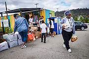 A woman carries food from the Free Store in Braddock, Pennsylvania, USA on April 23, 2016.<br /> <br /> Opened in 2012 by Gisele Fetterman, wife of Braddock Mayor John Fetterman, and housed in a shipping container on donated property, the store collects overstock supplies such as clothing and food, and provides them to needy people in the community free of charge.<br /> <br /> Partnering with organizations such as Heritage Community Initiatives and a New York City-based organization called Kids in Distressed Situations (KIDS) helps to fill the store with clothing for men, women, teenagers, children and babies, and other essentials such as towels, diapers and formula which are then given away to anyone who needs them.<br /> <br /> The rules of the store are simple: Be kind. Take only what you need, and pay it forward.