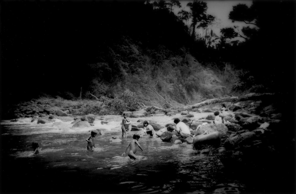 Agta Negrito women and children bathe in rainforest stream as typhoon approaches in the Sierra Madre Mountains of Luzon, Philippines.