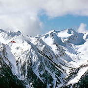 A US Coast Guard helicopter from USCG air station Port Angeles passes the Bailey Range of peaks in Olympic National Park. Seen from Hurricane Ridge, ONP.