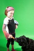 Young girl of 8 feeding her dog a carrot on green background Model and Property releases available