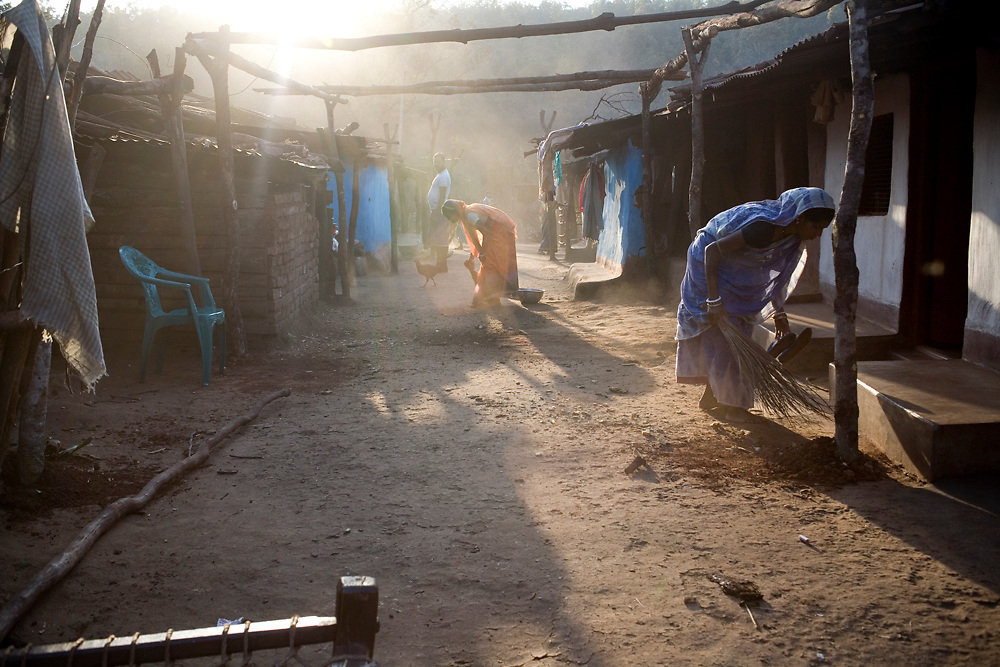 Women sweep in front of their homes in Longalata village in the chromite mining belt of Orissa. Keonjhar, Orissa, India.