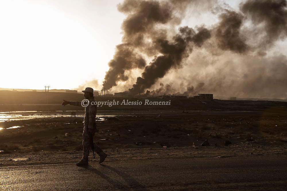 Iraq, Qayyara: An Iraqi army soldier gestures to people approaching the northern check point in Qayyara. <br /> On the backdrop is visible the smoke of the crude oil fields that IS fighters set on fire as they retreated from the city. Alessio Romenzi