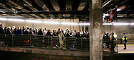 A New York City police officer, right, keeps a line of people at bay in Grand Central Station as they wait for a commuter train during the transit stirke that paralyzed New York on 21 December 2005 .