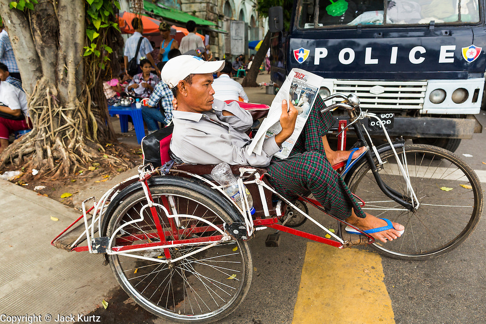 04 JUNE 2014 - YANGON, YANGON REGION, MYANMAR: A man reads a newspaper in front of a police van in Yangon, Myanmar (Rangoon, Burma). Yangon, with a population of over five million, continues to be the country's largest city and the most important commercial center.     PHOTO BY JACK KURTZ