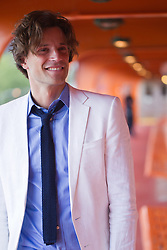 man in a white suit smiling