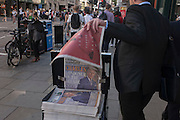 A businessman takes a free newspaper with the headline featuring a portrait of Prince Charles, the Londoner of the decade, according to the Evening Standard, in the City of London, England UK.