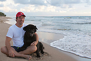 handsome middle aged man sitting on the beach with his black Chow dog