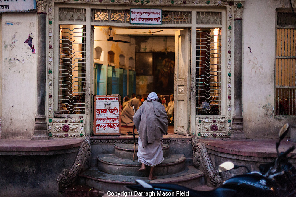 A widow climbs the steps to the one of the dilapidated buildings of the Sri Bagwan Bhajan Ashram as the evening session of chanting ends.  The sessions are divided into morning and evening sessions of four hours each getting between Rs10 to Rs18 per day about 15 cent US.  The Ashrams are very protective against photography which would imply they are aware of the exploitive nature of what they do as above the this ashram and in ashram owned properties the Widows rent meagre, sub standard over crowded rooms for about Rs250.