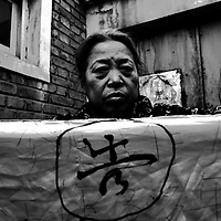 BEIJING, DECEMBER-22:  a woman who retired 17 years ago and has never been paid and pension, holds a banner.. Hundreds of thousands of Chinese have descended upon Beijing in the past decades hoping to get the attention of higher authorities for cival law cases reaching from work accidents, violence against family members, murder,  money extorsion and which in the majority reveal a corrupt rural legal system...The tradition of  appealing to higher authorities  in the capital reaches back to imperial times . In Beijing , petitioners villages where people would congregate in cheap housing, outside the city centre were common. These days though, petitioners increasingly face tremendous obstacles to get heard : provincial as well as undercover police try to stop petitioners from going to the National Petition offices to file law suites . If caught, they are briefly sent to an unoffical detention centre where they wait for the train ride back to the province.  In addition  the number of villages has been reduced significantly as the preparations for the 2008 Olympics progress. Many fear they will be all gone  by summer 2008. ..