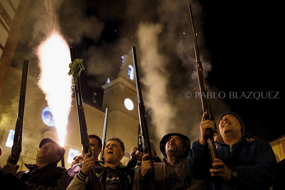 "Revelers shoot blanks with their guns during the ""La Encamisa"" Festival on December 7,  2014 in Torrejoncillo, Extremadura region, Spain. ""La Encamisa"" is an ancient festival in honor of Immaculate Conception. Hundreds of horsemen wearing a white sheet gather outside the church in the main square. The procession starts when a banner with the image of Immaculate Conception is delivered to the horse rider steward and people cheer and shoot blanks. There are bonfires along the way where people gather to chat, eat traditional sweets and drink local wine. The origin of this tradition is unknown but it is believed the festival comes from a military event in which people from Torrejoncillo were involved. The war in Flanders in 1585, the Battle of Pavia or a legend of the siege suffered by city of Coria. (© Pablo Blazquez)"