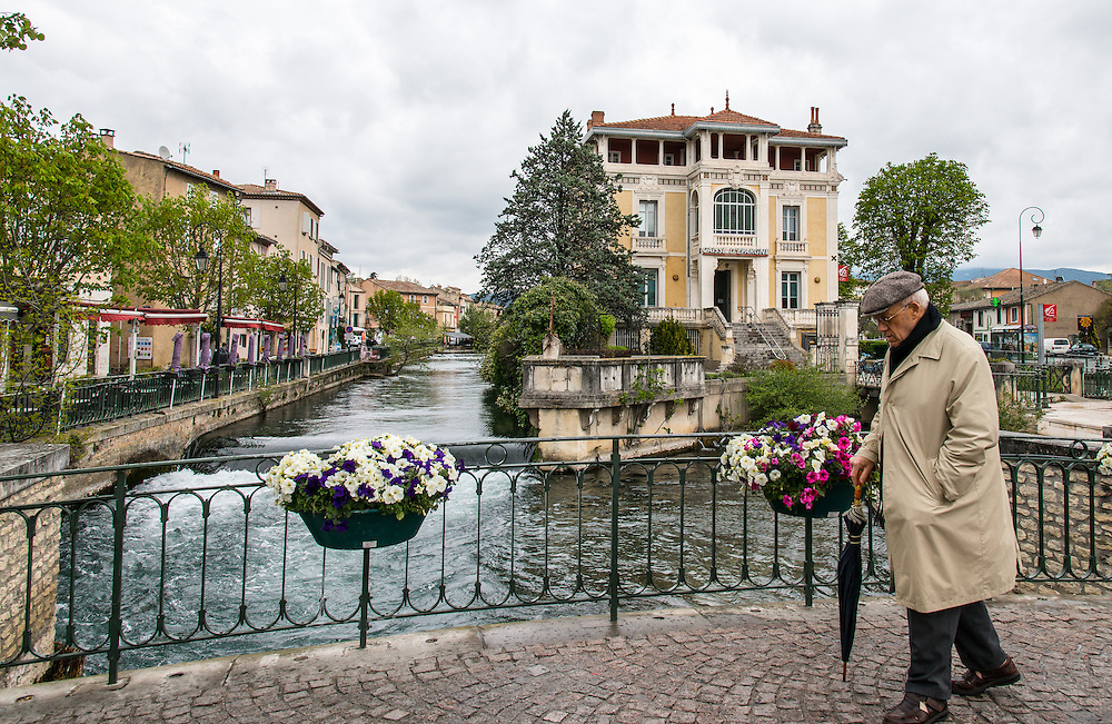 "The sombre appearance of the old man seems to match the cloudy day's atmosphere on L'Isle-sur-la-Sorgue  (the isle on the river Sorgue). Also known as  the ""Venice of Frnace"",  several parts of the city are separated by the river's  tributes, making it a very picturesque location."