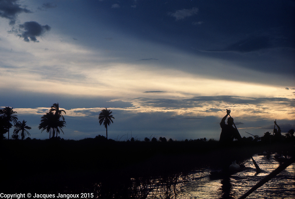 Africa, Ngiri River islands, Democratic Republic of the Congo, Libinza tribe. Men in canoes paddling in swamp savanna on Ngiri River at dusk.